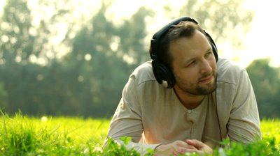 stock-footage-man-with-headphones-listen-to-the-music-on-the-meadow